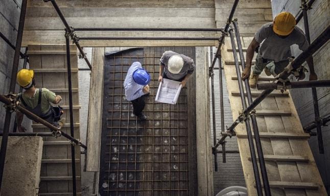Visão de cima de trabalhadores da construção civil em uma obra.